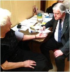 Barry from the Stroke Association gives a blood pressure check to an older dancer