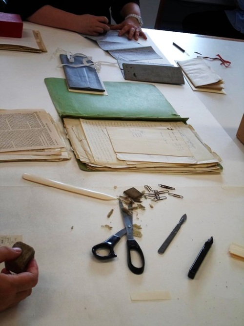 Archive documents being cleaned and paper clips replaced to prevent future damage